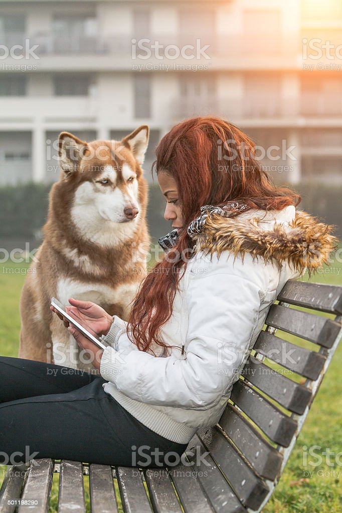 Young woman with tablet and her dog stock photo