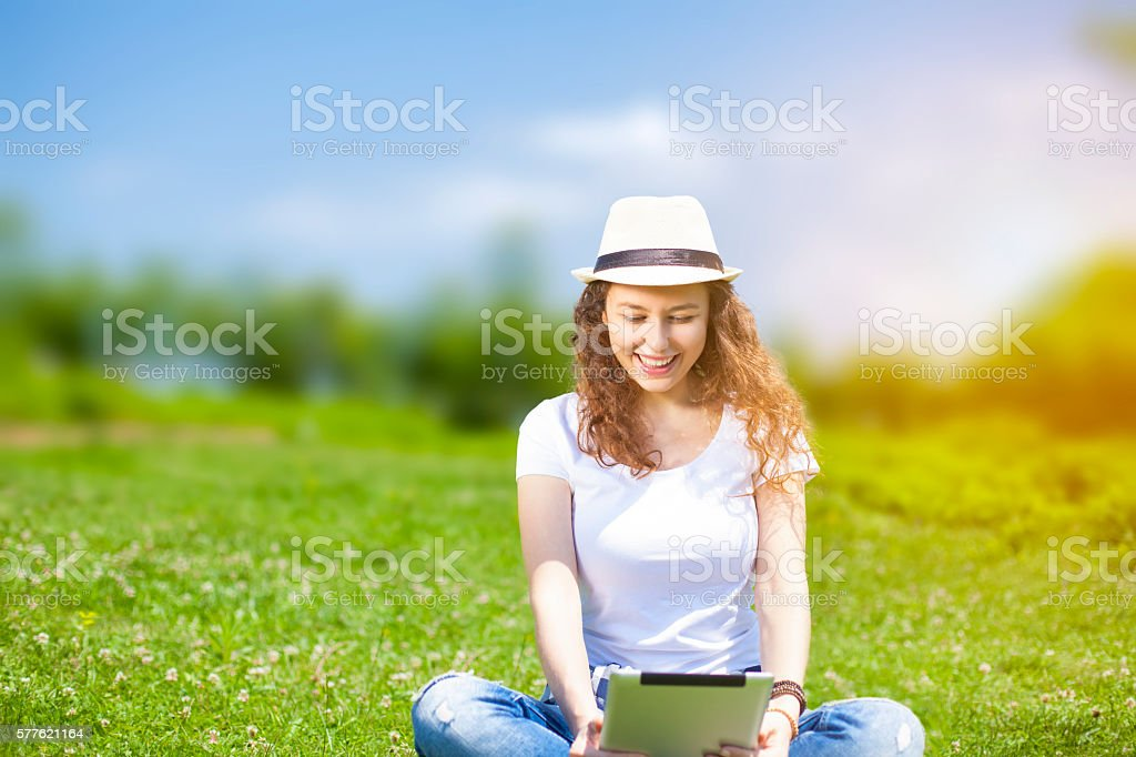 Young woman with tablet in summer stock photo