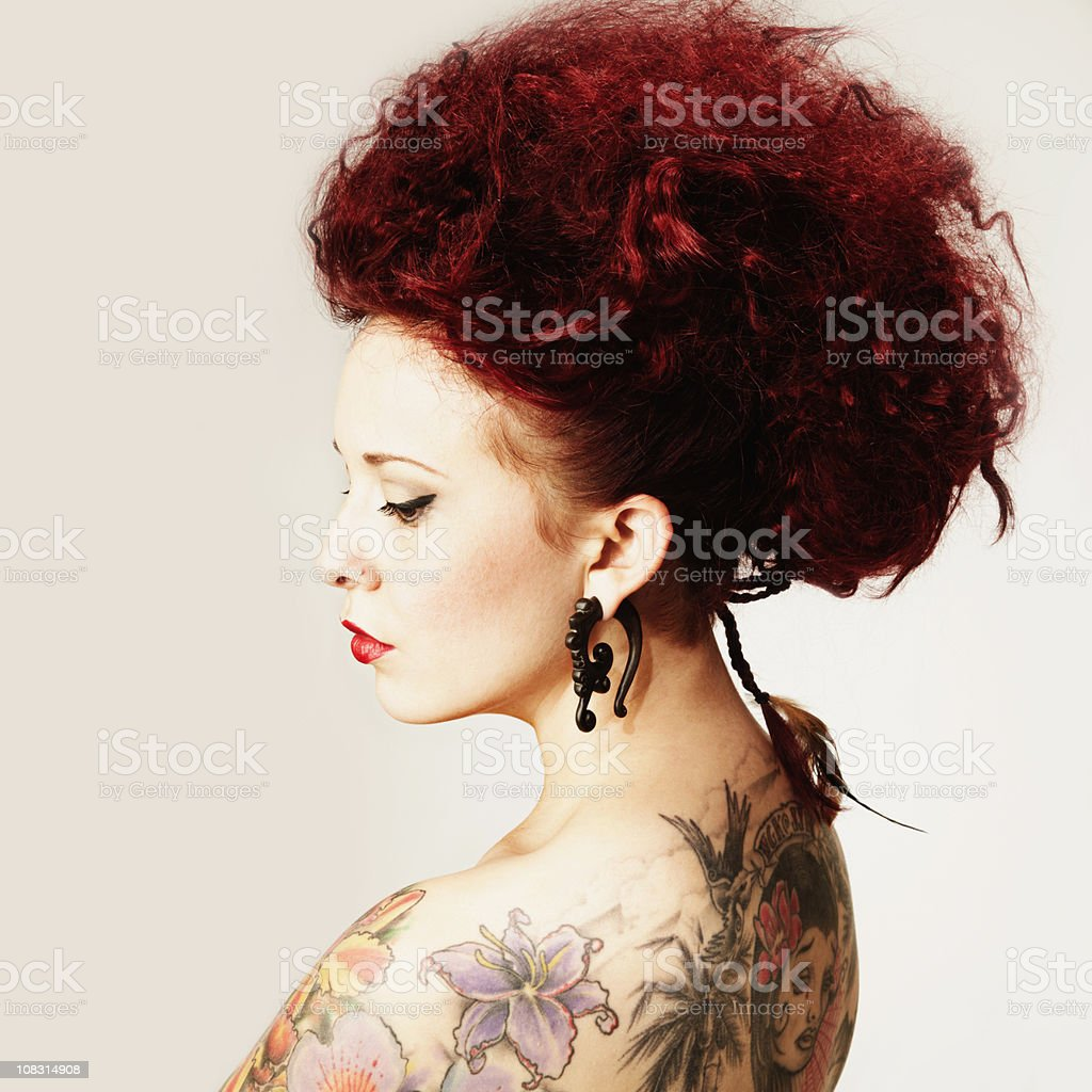 Young Woman with Tattoos and Tribal Ear Rings. Isolated stock photo