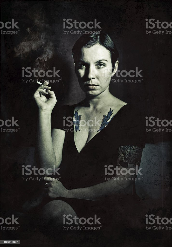 Young woman with tattoos smoking a cigar stock photo