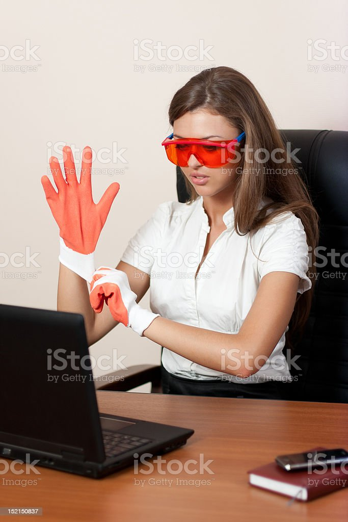 young woman with the laptop in gloves and orange glasses royalty-free stock photo