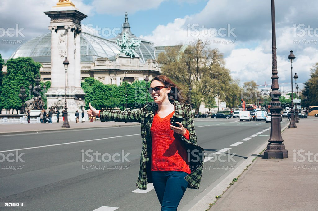Young woman with thumb up for hitch-hiking at Chapms Elysees stock photo