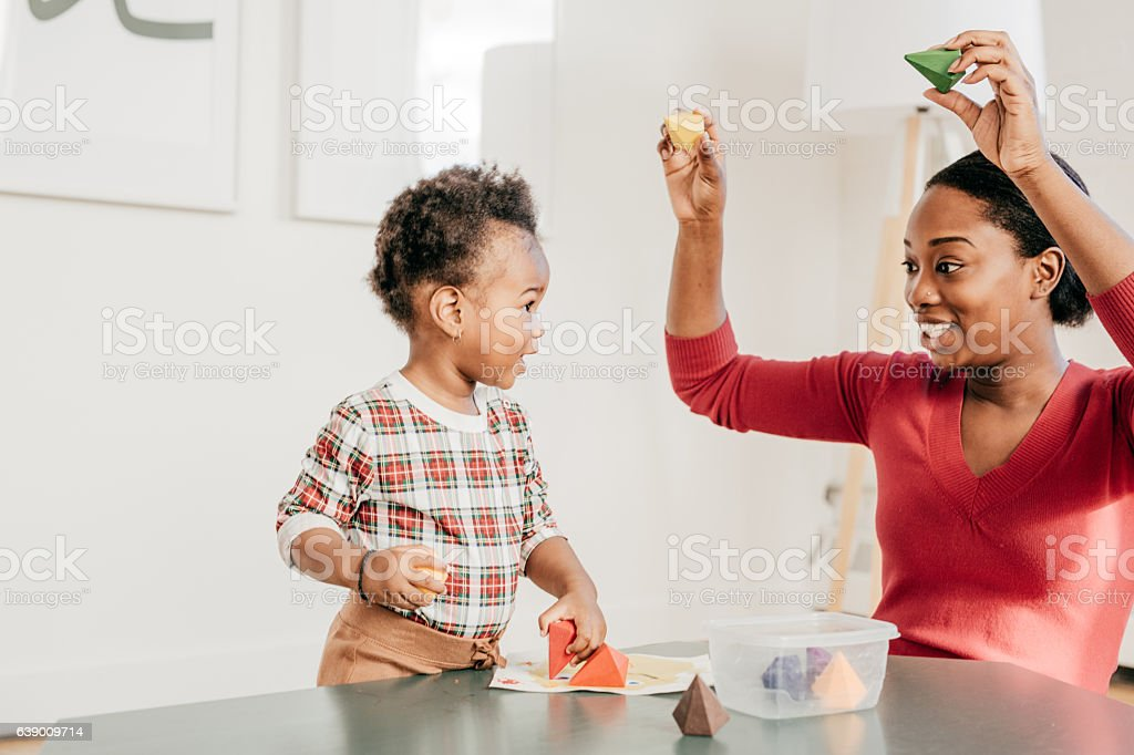 Young woman with toddler playing with toys stock photo