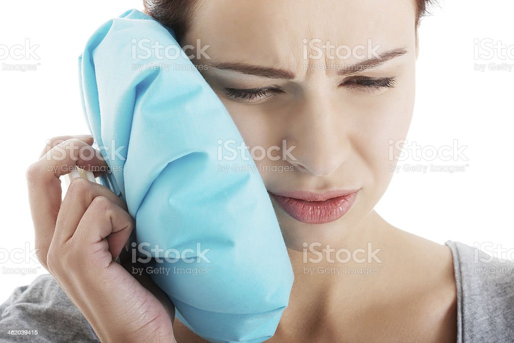 Young woman with toothache and ice bag. stock photo