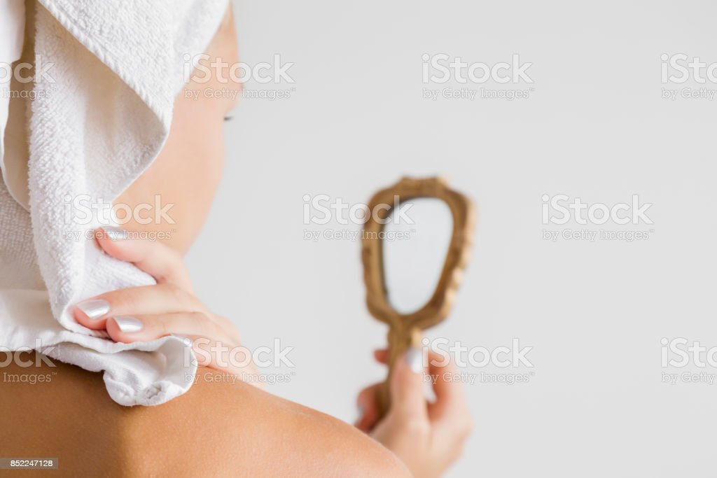 Young woman with towel on the head after shower looking at the mirror on the gray background. Cares about a body skin and face. stock photo