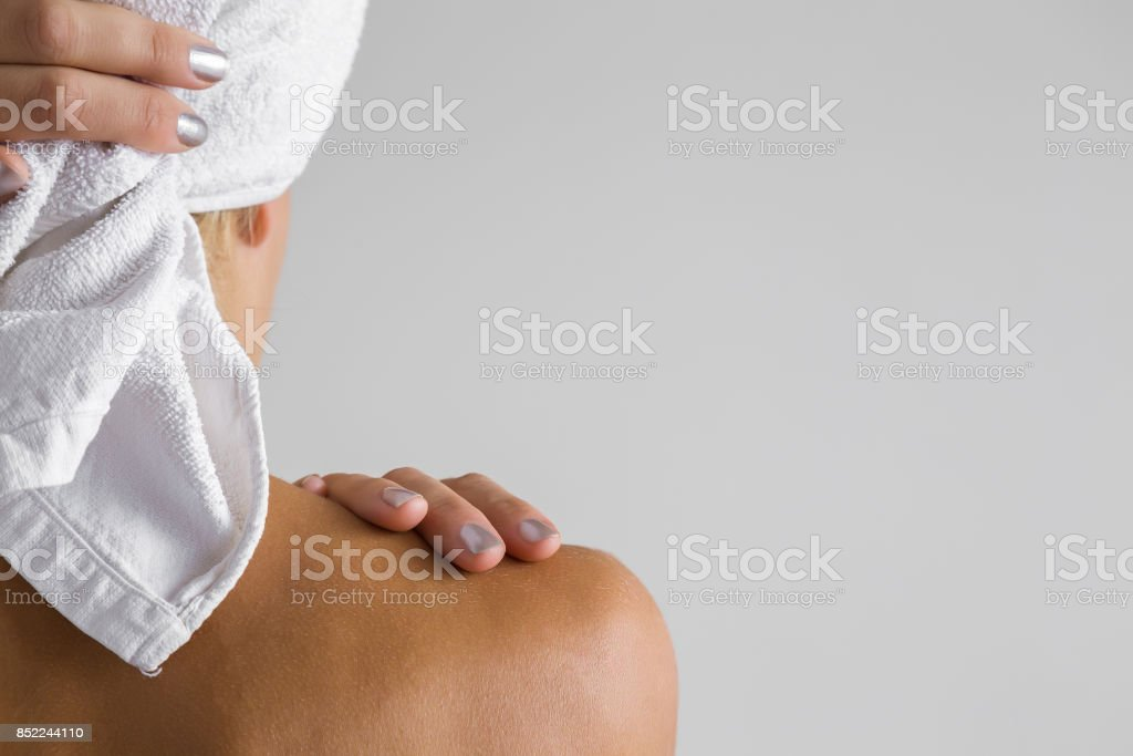 Young woman with towel on the head and naked shoulder after shower. Empty place for a text on the gray background. stock photo