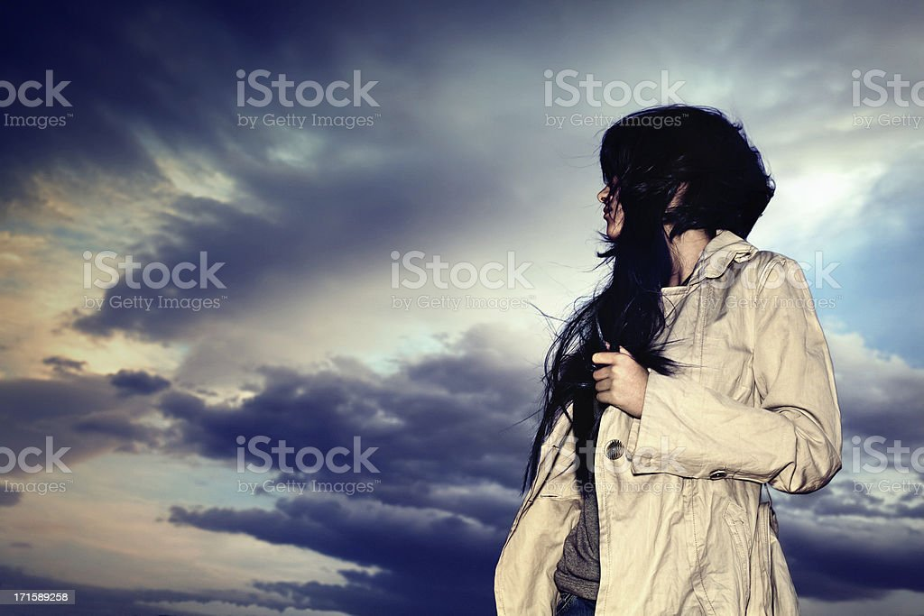Young woman with trench coat against a dark moody sky stock photo