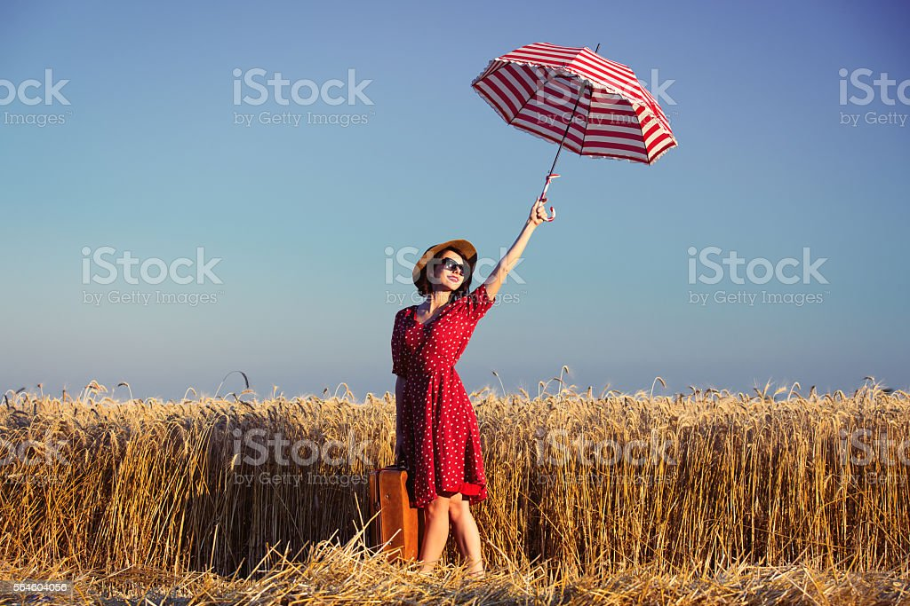 young woman with umbrella and suitcase stock photo