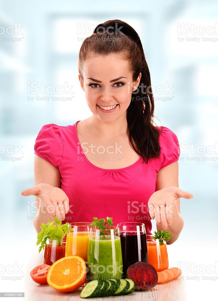 Young woman with variety of vegetable and fruit juices stock photo