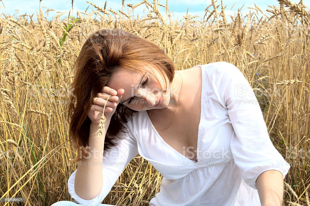 Young woman with wheaten spike in the gold field royalty-free stock photo