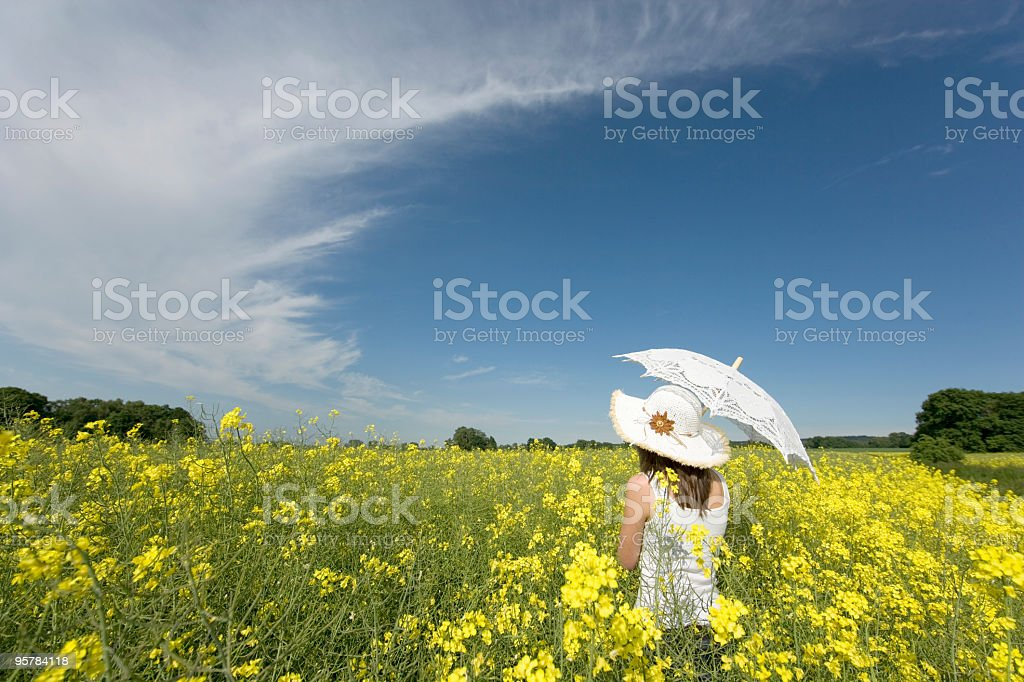 Young woman with white parasol in canola field royalty-free stock photo