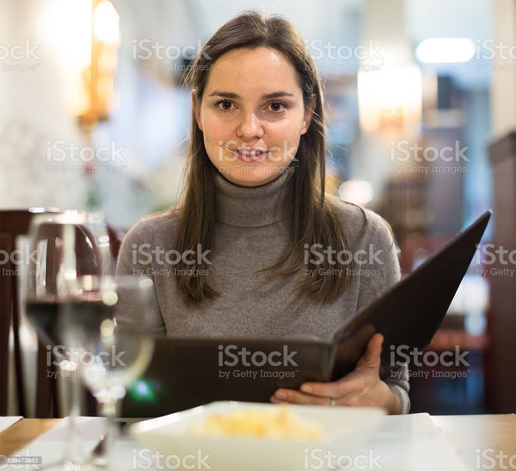 Young woman with wine looking at menu stock photo