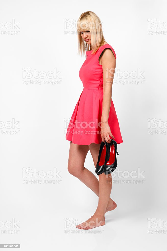 Young woman with wounded heels holding shoes royalty-free stock photo