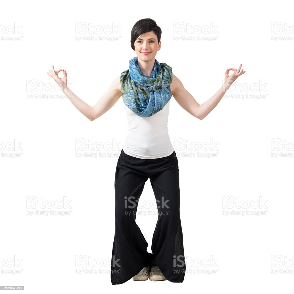 Young woman with yoga mudra hand gesture smiling at camera stock photo