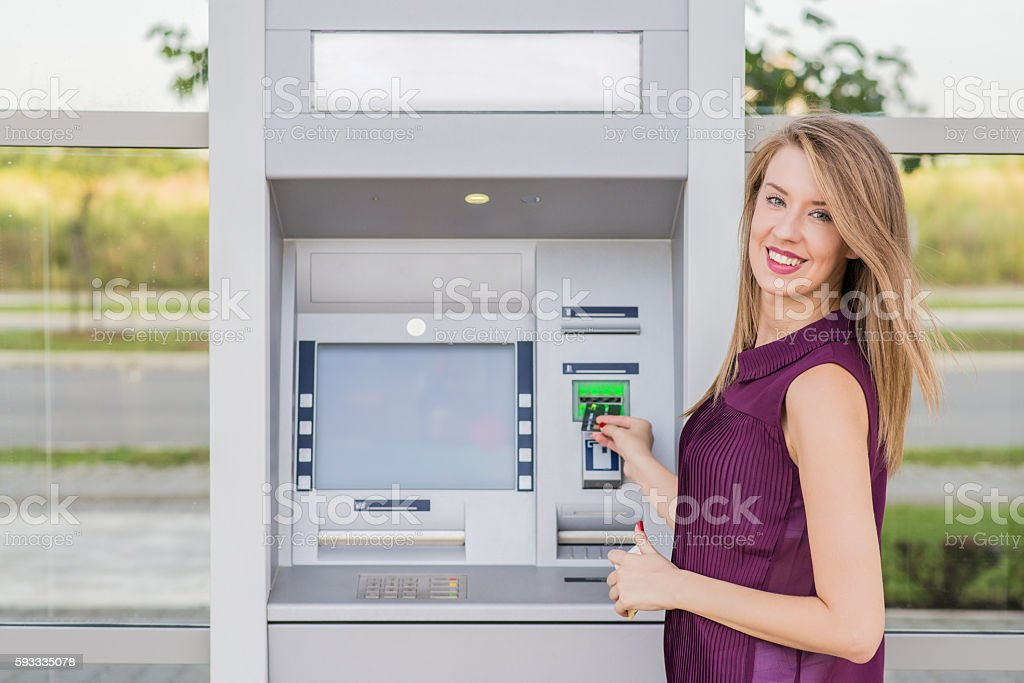 young woman withdrawing cash at the atm stock photo