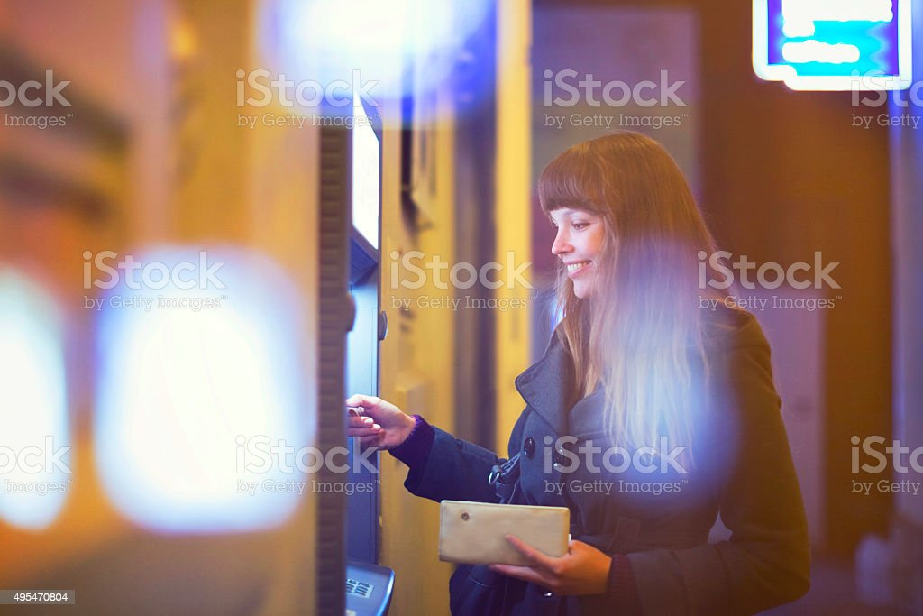 Young woman withdrawing cash from ATM stock photo