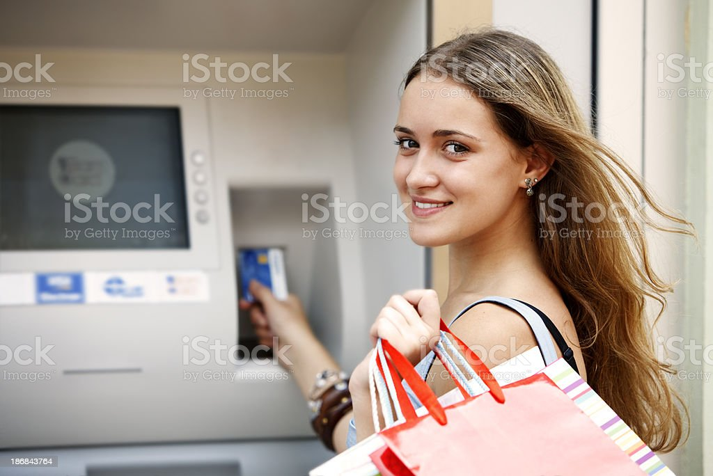 Young woman withdrawing money from credit card with ATM royalty-free stock photo