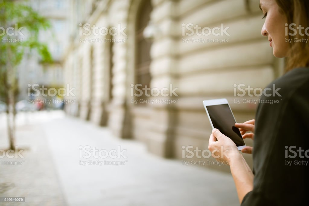Young woman woman using her Mobile Phone on the street stock photo