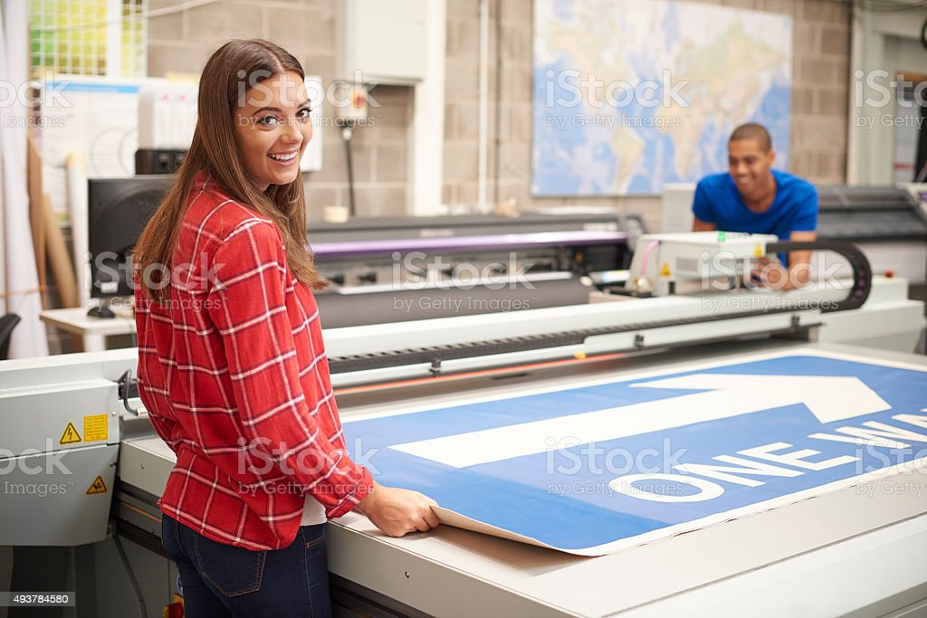 young woman working at a digital printers stock photo