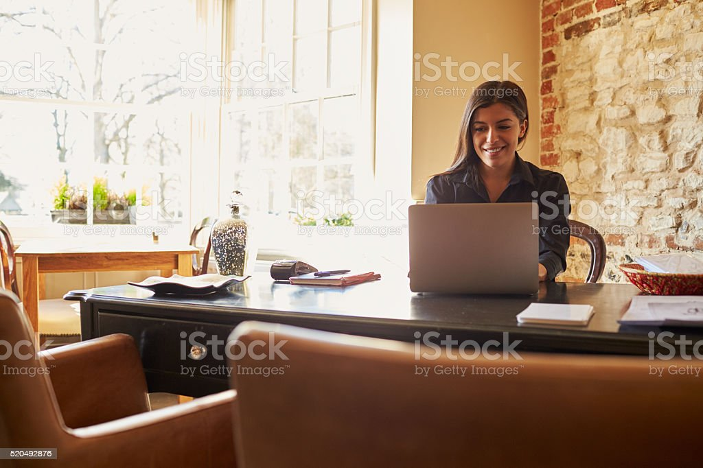 Young woman working at the check-in desk of a boutique stock photo