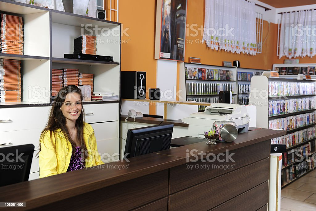 young woman working at the video store stock photo