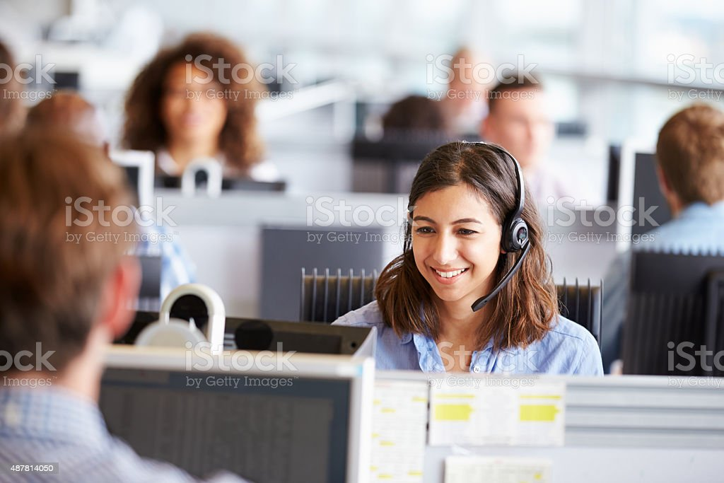 Young woman working in call centre, surrounded by colleagues stock photo