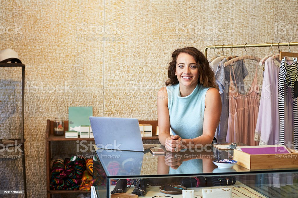 Young woman working in clothes shop leaning on counter stock photo