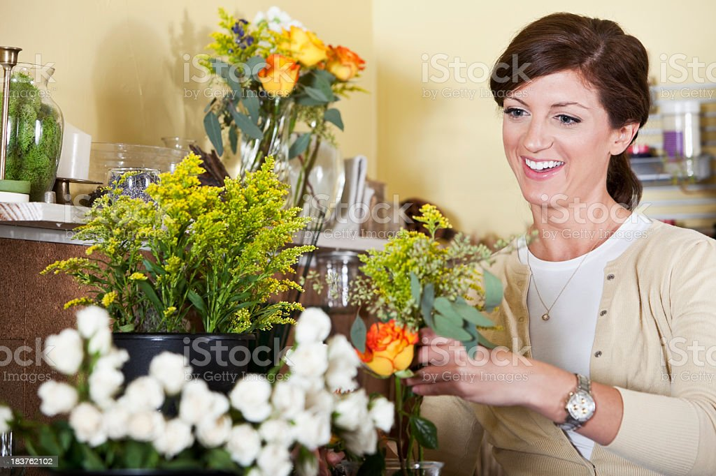 Young woman working in florist shop arranging flowers stock photo