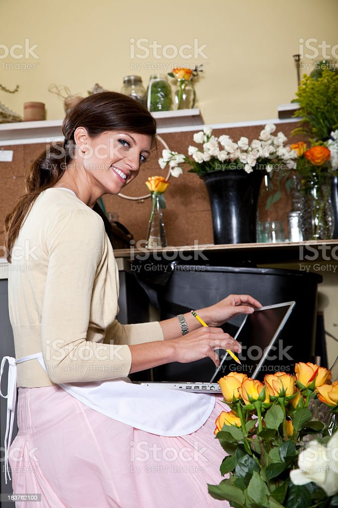 Young woman working in florist shop with laptop stock photo