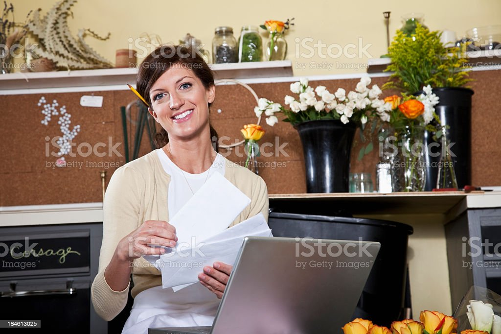 Young woman working in florist shop with laptop royalty-free stock photo