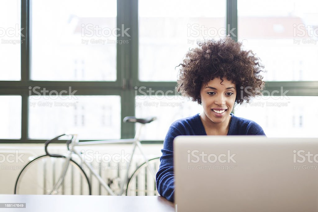 Young Woman Working in Loft Space Behind Laptop stock photo
