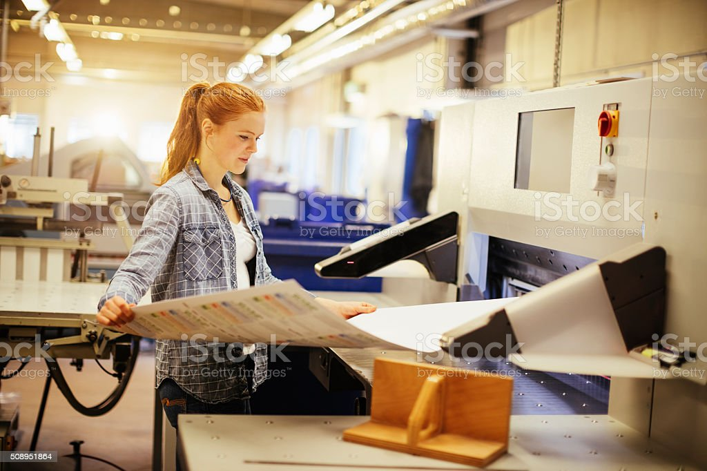 Young woman working in printing factory stock photo