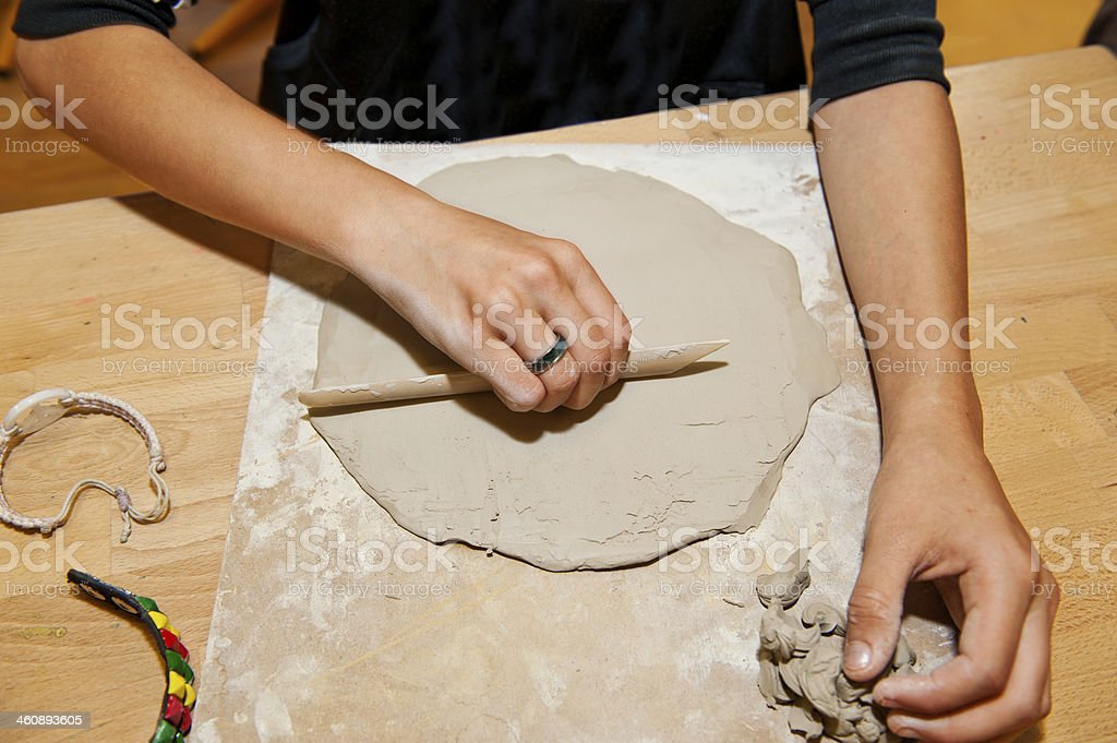 Young woman working on clay on a wooden table stock photo