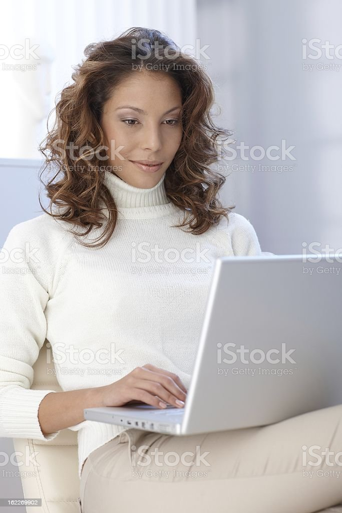 Young woman working on laptop at home stock photo