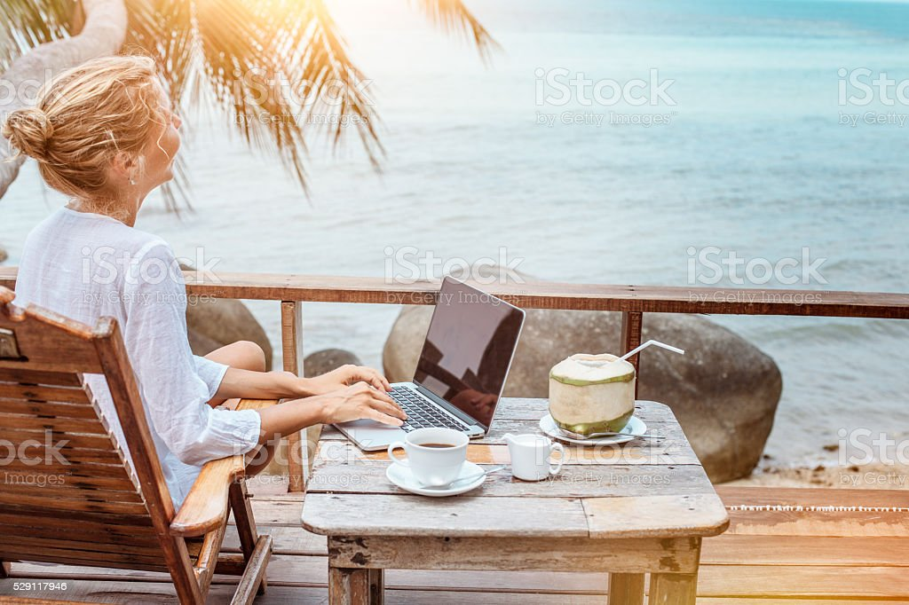 Young woman working on laptop with coffee and young coconut stock photo