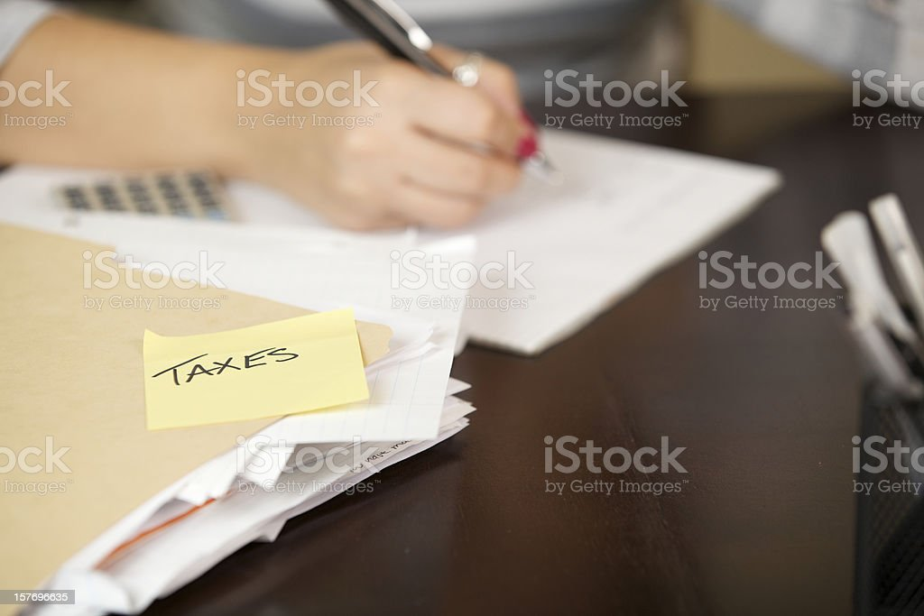 Young woman working on taxes stock photo