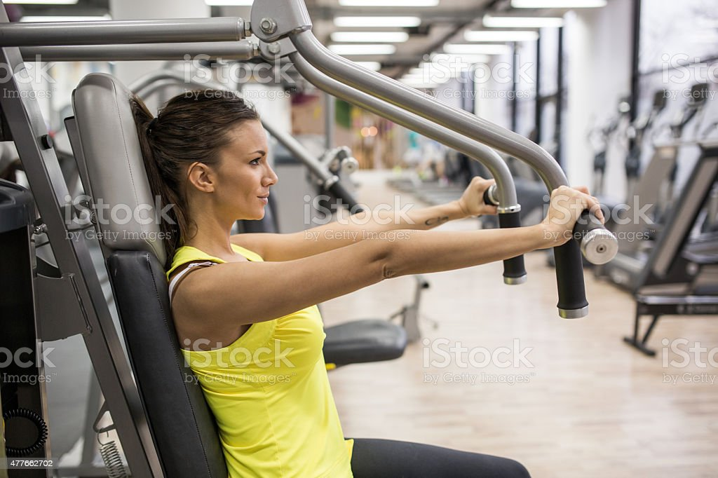 Young woman working out on exercise machine in a gym. stock photo