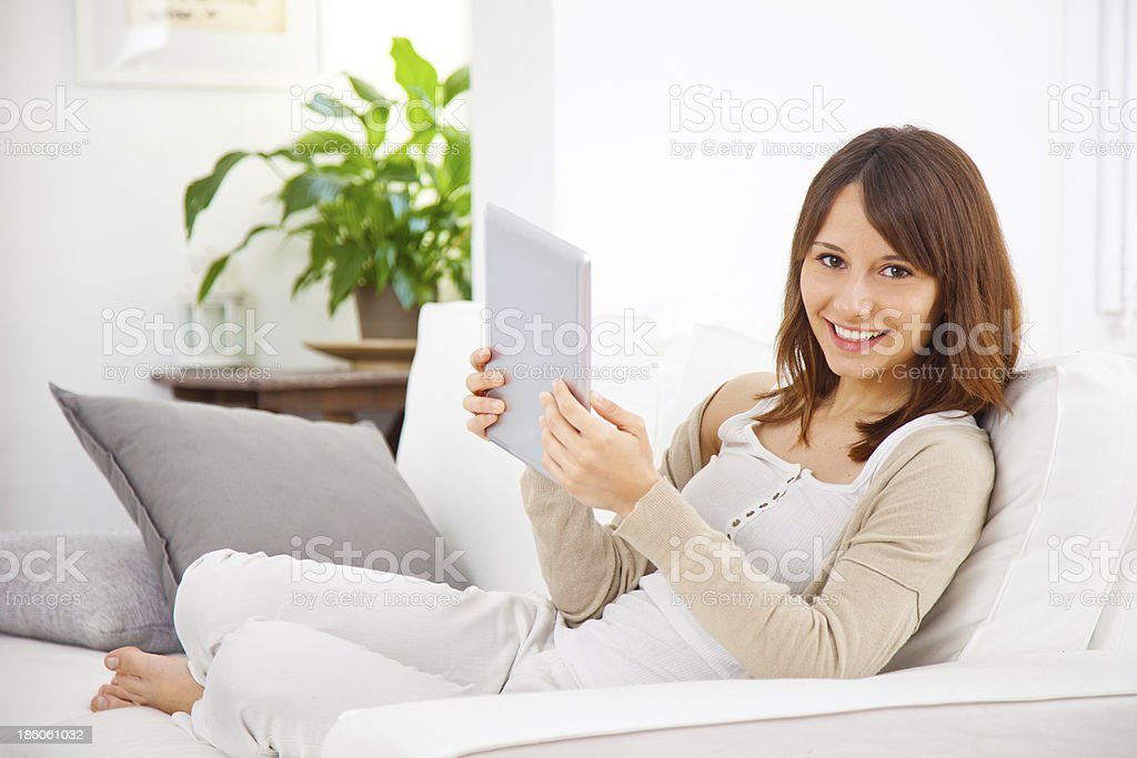 Young woman working with a digital tablet at home royalty-free stock photo