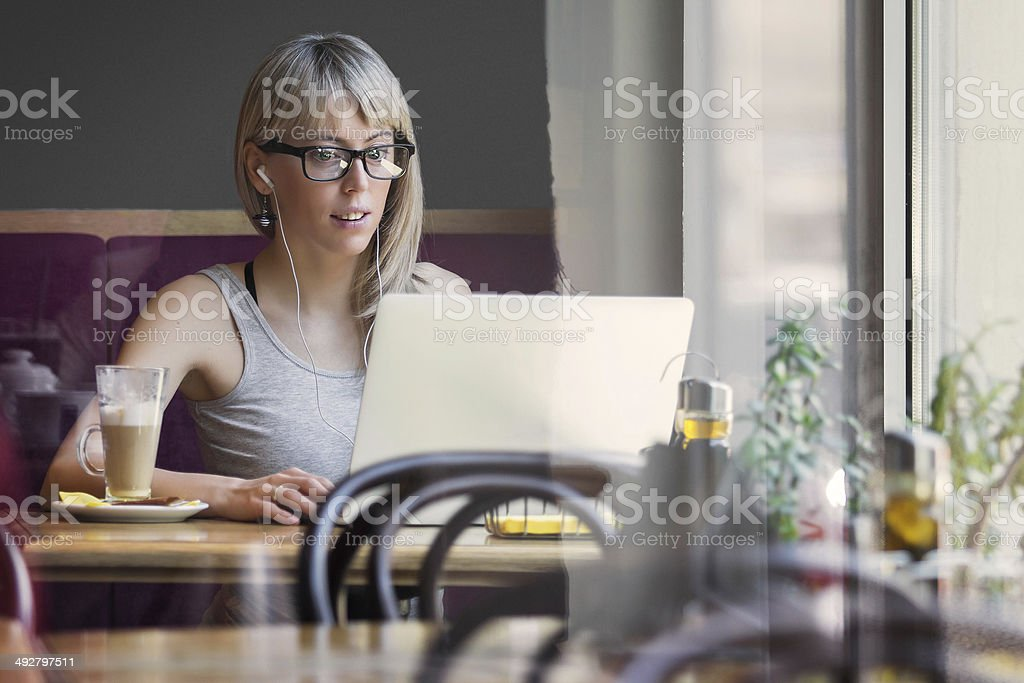 Young woman working with computer in cafe stock photo