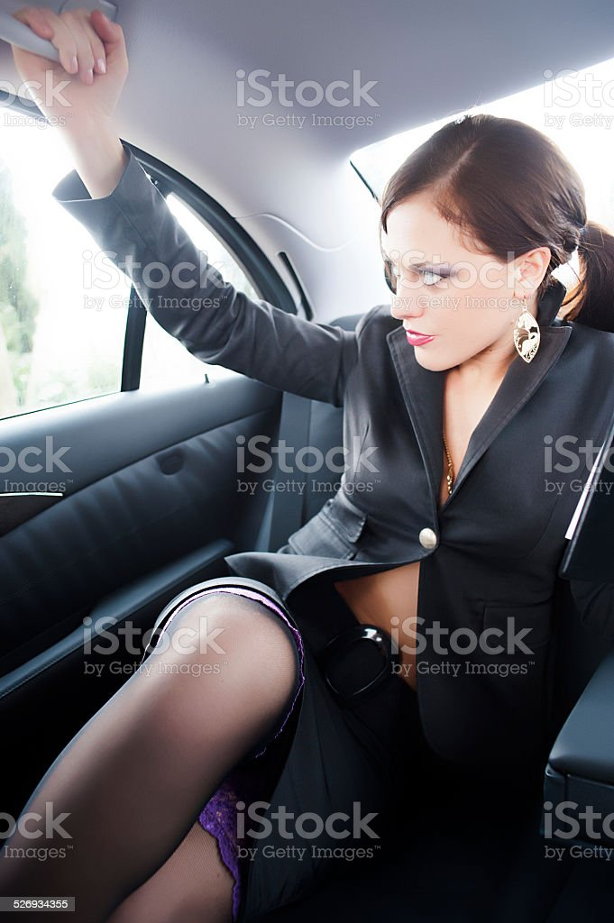 Young woman works from the backseat of a luxury car stock photo