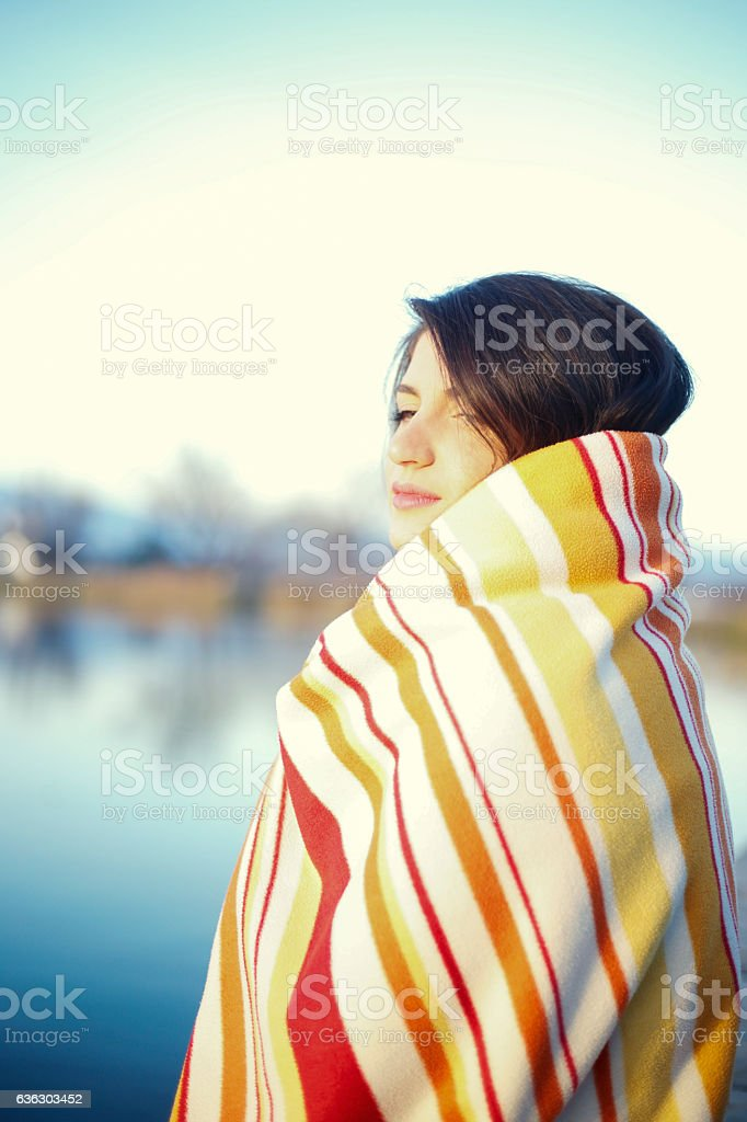 Young woman wrapped in a blanket relax on the pier stock photo