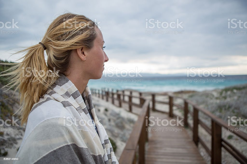 Young woman wrapped in blanket on the beach in Sardinia, Italy.