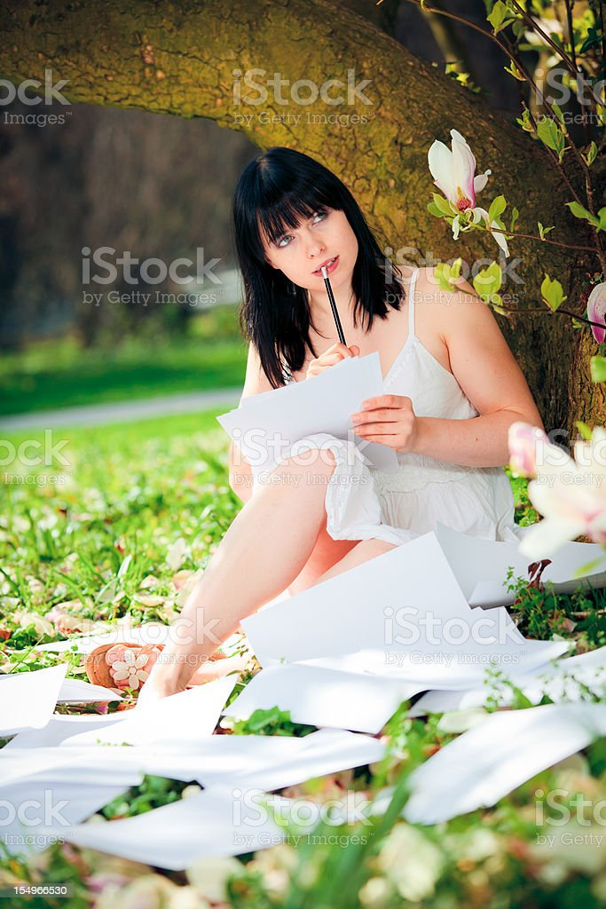 young woman writer sitting next to a magnolia tree royalty-free stock photo