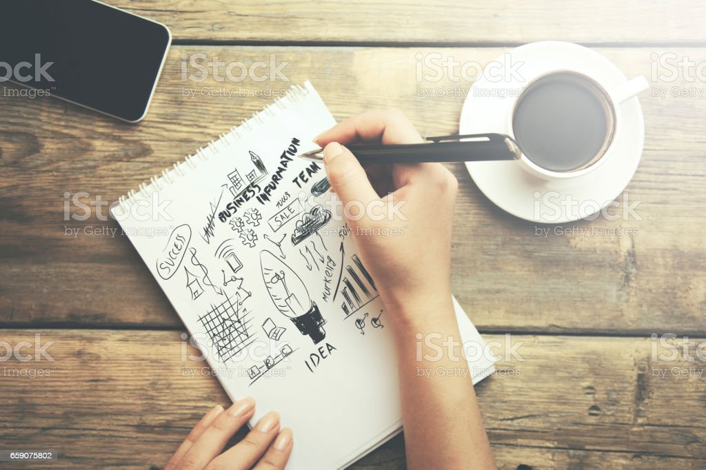 Young woman writes to diary on a wooden table stock photo