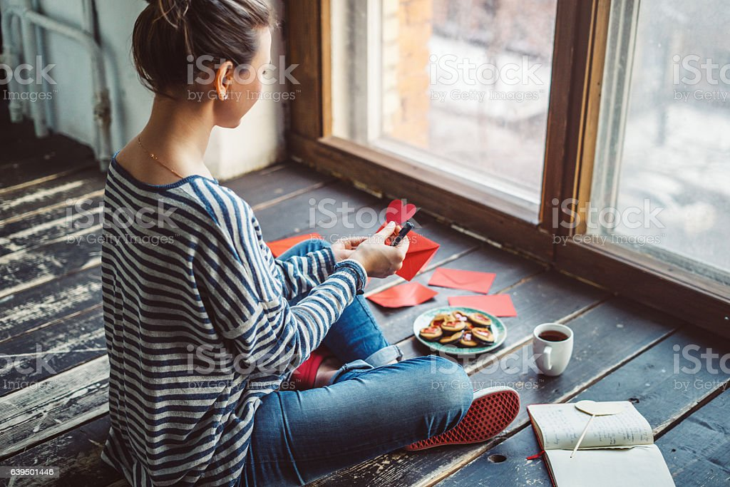 Young woman writing a valentine card stock photo