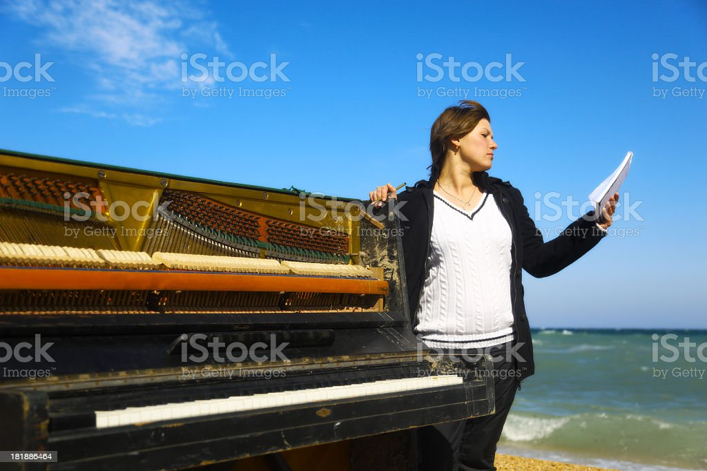 young woman writing and an old piano on the beach royalty-free stock photo