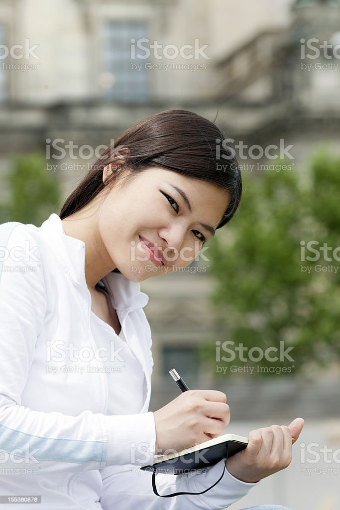 young woman writing in diary, Berlin Germany stock photo