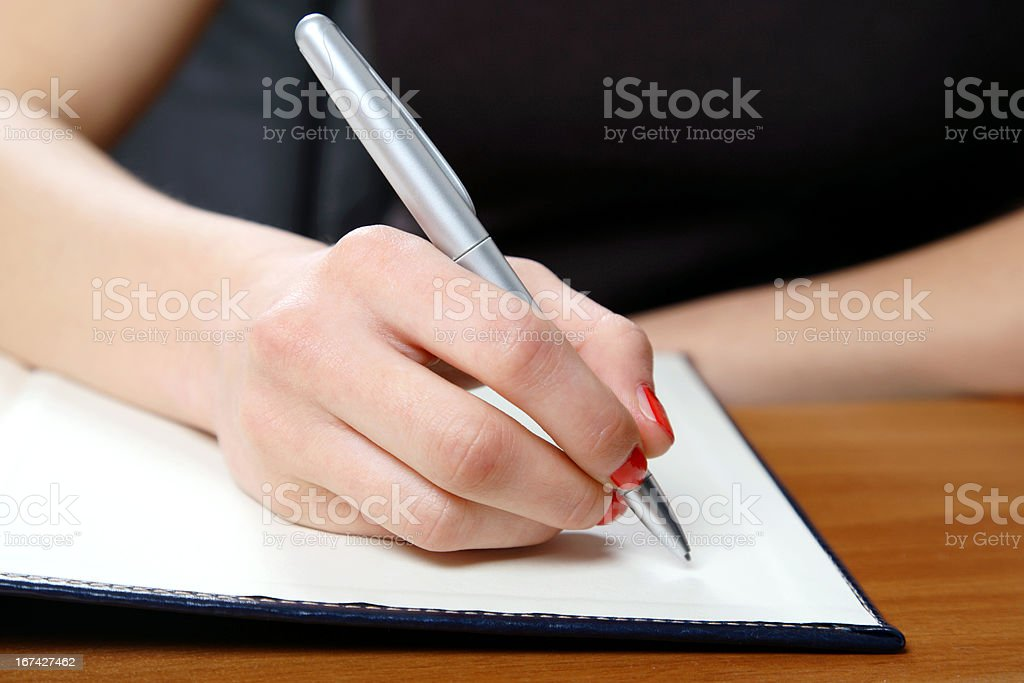 Young woman writing in office royalty-free stock photo