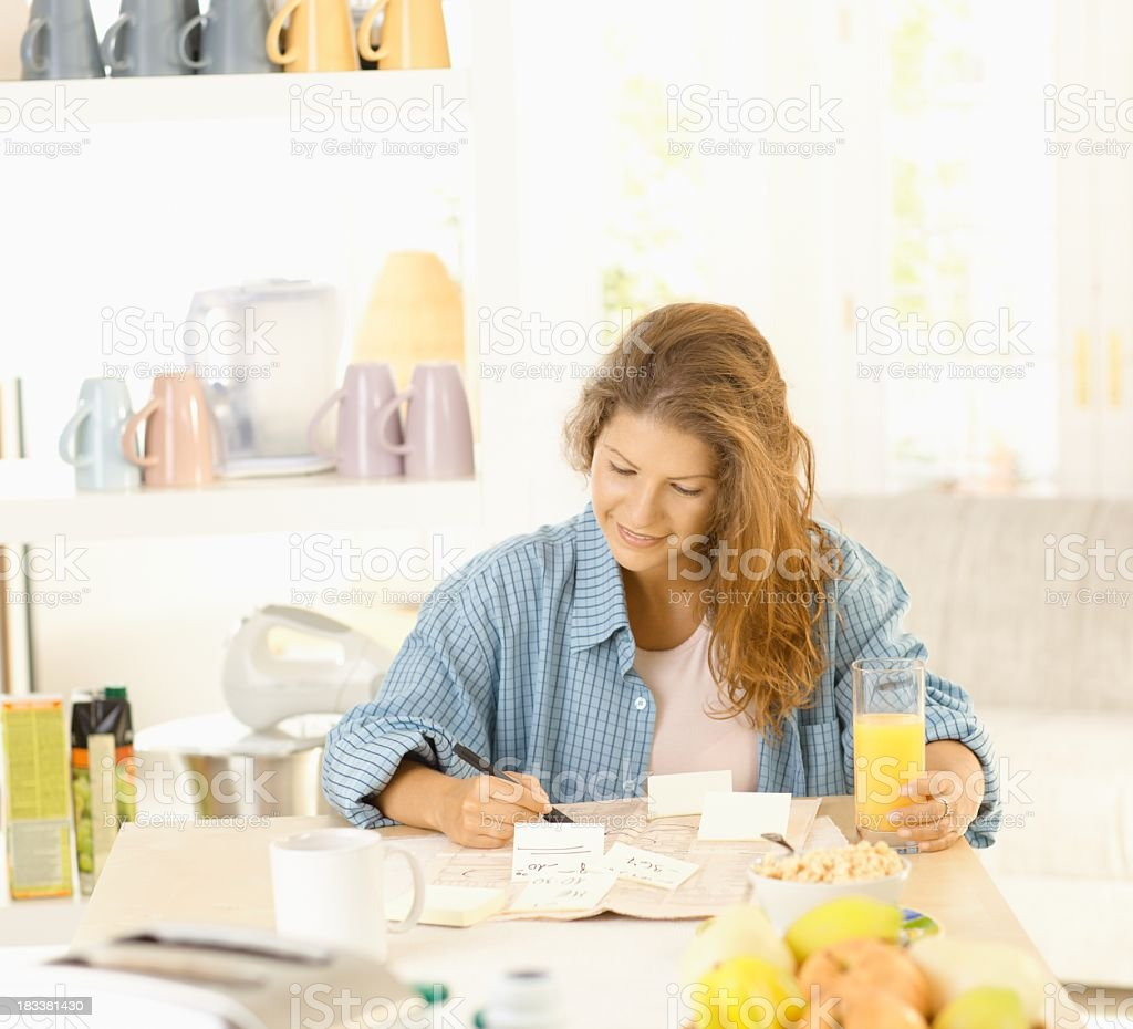 Young woman writing notes in kitchen royalty-free stock photo