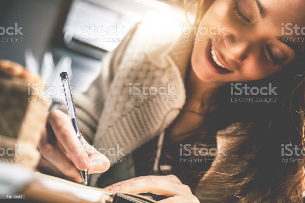 Young woman writing on diary stock photo